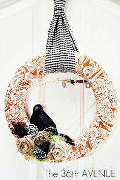 I like how the black/white fabric is used as the wreath hanger.  (Not crazy about the orange fab though.)