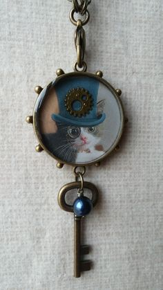 """""""Steampunk Kitty"""" bezel filled with paper, gear, and topped with liquid resin.  Can be used as an ornament or necklace.  Want to see more?  https://www.etsy.com/shop/BezelsandBeyond"""