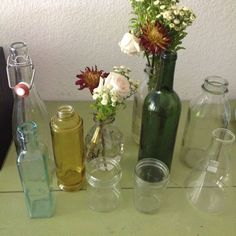 Assorted bottles and jars for flowers, some hanging from trees with divine twine.