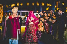 A stunning walk down the aisle holding her ghoonghat (veil) for Bride Nazuk of WeddingSutra. Photo Courtesy- Ramit Batra