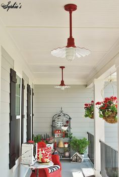 Pops of red, including super cool fixtures from Lights Unlimited Inc., add punch to the front porch of this light gray farmhouse.
