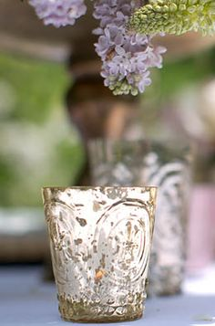 3.99 SALE PRICE! These mercury glass votive holders in silver feature a classic Fleur-de-Lis pattern supported by a hobnail base. Each silvery votive cup mea...