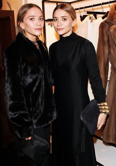 Mary-Kate Olsen wearing a black fur coat and Ashley Olsen wearing a black long-sleeve turtleneck dress