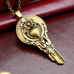 A brass key embellished with a bronze art nouveau heart and scrollwork, finds new life as a pendant. Maybe it can unlock someones heart... or your own.    The pendant (key) is 1 3/4 inches long and is hung on an approx. 19 inch bronze chain with a lobster claw clasp.