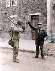 A Frenchman offers a glass of wine to an Ameirican heavy gunner in Coutances, France, July 1944.