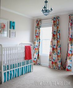 Baby Girl Nursery with DIY curtains in bright, graphic fabric, DIY crib skirt and DIY chandelier at www.viewalongtheway.com
