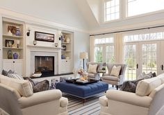 """High, vaulted ceilings, lots of light, palest blue with cream trim, woven cotton striped rug, a mix of cream and blue upholstered furniture - I love that this comfortable family room is just beach house-y enough but doesn't say """"HELLO YOU ARE AT A BEACH HOUSE SEASHELLS SEASHELLS STARFISH"""" like many unfortunate others."""