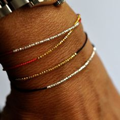 Delicate gold or silver ( choose from the menu bar) and red silk bracelet with the tiniest of tiny faceted beads gives the illusion of one continuous bar of spark. Extremely feminine and perfect on its own, easy to wear day or night Pretty tassel finish at the ends - Details: