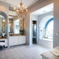"""""""The master bathroom offers a study in grandeur with its Calacatta gold hones marble countertops and mosaic stone floors. The tub is framed in an arched window. A Julie Neill chandelier illuminates the room.""""    with www.parisfinds.com  http://www.myneworleans.com/Louisiana-Life/November-December-2013/Home-Made-in-Louisiana/"""