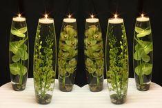 centro de mesa com vidros, velas e folhagens.