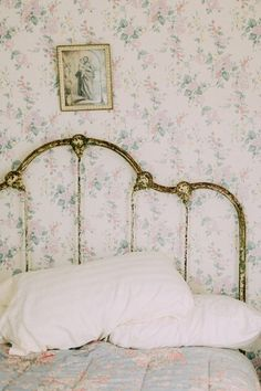 Vintage cottage bedroom style with wallpaper and iron bed, cabbages and roses quilt