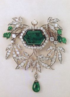 An early 19th century emerald and diamond Devant de Corsage, French. Centring a hexagonal emerald, surrounded by brilliant-cut diamonds, flanked by branches set with brilliant-cut diamonds and emeralds, suspending a pear-shaped emerald drop. Known to have been part of the collection of the Duke of Leuchtenberg.