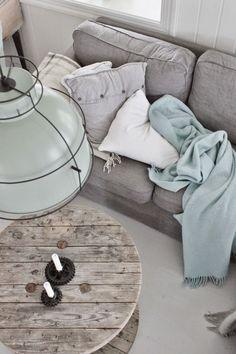 Grey sofa, soft aqua blanket, plaid throw, rustic spool table and vintage light