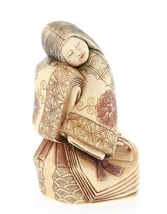 A JAPANESE CARVED IVORY OKIMONO The carved ivory okimono depicting a robed…