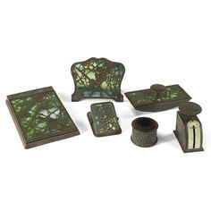 TIFFANY STUDIOS A GLASS AND PATINATED BRONZE `GRAPEVINE' DESK SET each piece decorated with fruiting vine against a mottled green and white glass ground comprising: note pad cover, calender frame, pen wipe, blotter, postal scale and letter clip Quantity: 6 stamped marks, `TIFFANY STUDIOS, NEW YORK'  and numerals including `971, 981 and 872' circa 1910
