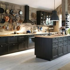 Black kitchen cabinets agains exposed brick for a warm and elegant look. Hanging pots and pans on the wall is a great space-saving idea!