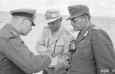 Field Marshal (Generalfeldmarschall) Erwin Rommel and Colonel (Oberst) Fritz Bayerlein. The officer on the right seems to be the commander (Major) Ziegler.