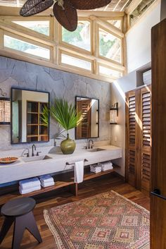 Hawaiian style house in Punta Sayulita. Master en-suite bathroom. His & her's sinks. Stone wall. Folding doors. Open towel shelves. Mexico.