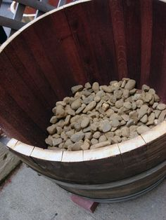 how to: wine barrel gardening - drill holes in the bottom of barrel. place on top of rocks or 3-4 bricks. add some rocks in the bottom to help with better drainage. fill with soil and compost. add plants or seeds and water.