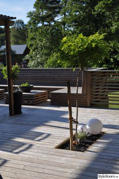 trädäck,klotlampa,stenrabatt,platsbyggd soffa,stenrabatt i altanen