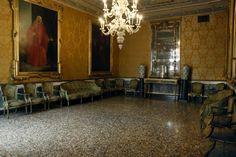Salotto verde. Nella sala, disposti attorno alle pareti -secondo l'uso veneziano- divani, sedie e poltroncine in legno laccato verde oliva decorati a mazzetti di fiori policromi e dorati. #salottoverde #querinistampalia