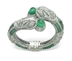 AN EMERALD AND DIAMOND CHIMERA BANGLE - The hinged bangle designed as pavé-set diamond hoops alternating with lines of emerald beads, to the two stylized dolphin head terminals, each holding a cabochon emerald in its mouth, inner diameter cm Emerald Bracelet, Emerald Jewelry, Gems Jewelry, Art Deco Jewelry, Diamond Jewelry, Turquoise Bracelet, Jewelry Box, Jewelry Bracelets, Vintage Jewelry