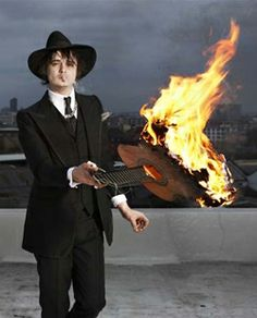 Pete Doherty wearing a black Edward Sexton suit holding a flaming guitar from the video to English rose