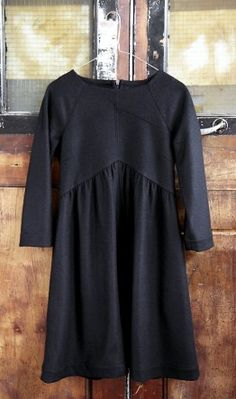 Black felted wool dress with high, gently gathered waistband and exposed gunmetal zip at the back. Bracelet length sleeves and 2 side pockets. Fully lined.