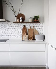 white matte kitchen with wooden chopping boards | open shelf | cube tiles and concrete floor