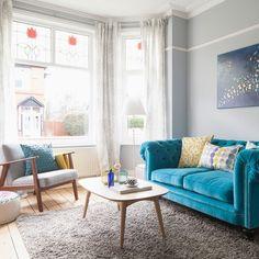 Un salon british coloré excentrique avec son canapé Chesterfield en velours bleu