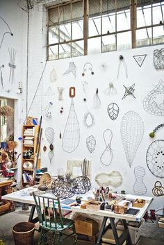 Collection on display on a wall in an art studio