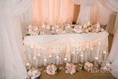 All the floating votive candles and pink floral bouquets hidden under drapery make for a gorgeous, intimate, head table at your wedding