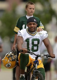 Green Bay Packers receiver Randall Cobb and Griffin Baierl, 13, from Ashwaubenon, ride to training camp practice on Friday, July 26, 2013. Evan Siegle/Press-Gazette Media