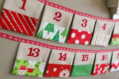 "Christmas Advent Calendar Fabric Pocket Bunting in by LooDeLoop, $100.00. This set consists of TWO 9.5 foot long buntings (each with 12 pockets) for a total of 24 pockets. Each ""flag"" measures approximately 4.5"" square with a 2.5"" tall pocket. The fabric pockets are a mix of holiday inspired fabrics in red and green featuring snowmen, snowflakes, chevron, stripes, Christmas trees and more. Actual fabric pockets may vary while remaining true to the color scheme shown."