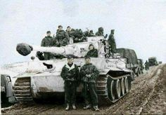A Tiger 1 crew posing with their machine which is allowing numbers of soldiers to hitch a ride in cold weather conditions