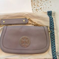 New Tory Burch Amanda Logo clutch NWOT Authentic Tory Burch Amanda Logo Clutch crossbody purse in Mercury Gray. Includes detachable gold chain and duster bag. Never used. Tory Burch Bags Crossbody Bags