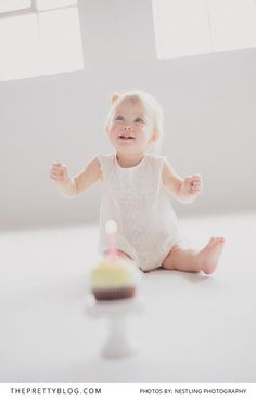 Happy one year old baby girl with a cupcake! See the full baby photo shoot on theprettyblog.com | Photography: Nestling Photography | Venue: Propstars Studio |