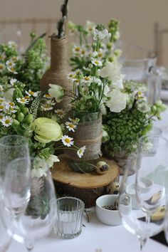 Rustic decorated jars and bottles | creative wedding inspiration | White and buttermilk yellow Spring style wedding flowers at Millbridge Court located in Frensham, Surrey. Created by Hannah Berry Flowers hannahberryflowers.co.uk