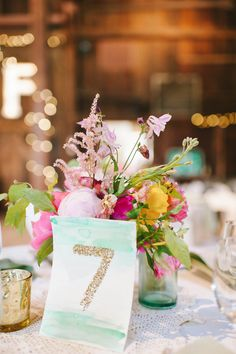 bright centerpiece with watercolor and glitter table number, photo by Michelle Gardella http://ruffledblog.com/glittery-webb-barn-wedding #weddingcenterpieces #tablenumbers