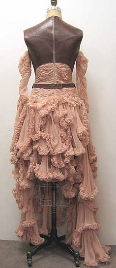 Dress  Alexander McQueen  (British, 1969–2010)    Date:      fall/winter 2002–3  Culture:      British  Medium:      silk, synthetic, leather  Dimensions:      Length at CB (a): 57 in. (144.8 cm) Length (b): 34 1/2 in. (87.6 cm)  Credit Line:      Isabel Shults Fund, 2007