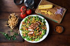 Kickin' Logan's Chickin' Salad | Blackened chicken over romaine, tomatoes, cheddar cheese, roasted corn, black bean salsa & tortilla strips, with homemade Roadhouse Ranch - at Logan's Roadhouse