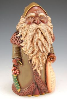 Black Father Christmas with Nice List- Black Father Christmas with Nice List. Beautifully designed and finished in old world sage with gold and fur trim, this African American Santa carries a stocking filled with candy canes and his nice list in his other hand. Susan's unique finishing of her Santa carvings give them a distinct old English, almost antique appearance.