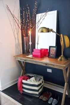 decoração de hall de entrada com mesa de madeira, espelho, parede azul petróleo, luminária dourada