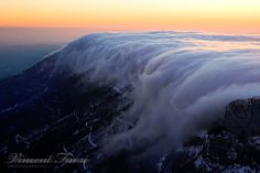 Tsunami (clouds rolling over a cliff in France) by vincentfavre.deviantart.com