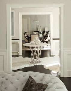 Chic foyer features a round white marble top table with a silver leaf base placed atop white cowhide rugs.