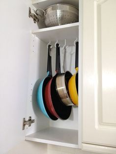 A neat way to store your pans is with screw-in cup hooks. For an overhead cabinet, line them up on the underside of a shelf, spacing them apart enough to ensure they'll each be easy to access.