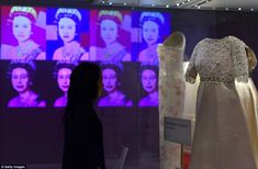 An exhibition assistant at Kensington Palace looks at a Hardy Amies dress that was worn by Queen Elizabeth II