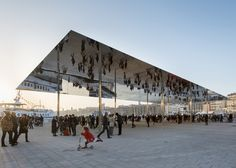 Events pavilion in Marseille harbour by Foster + Partners with polished stainless steel mirrored canopy that reflects visitors walking underneath.