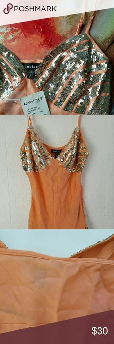 "NWT bebe Sequin Cami New with tags attached from bebe. Super sparkly gold and silver sequins make this coral cami really pop! 100% silk, and comes with little baggie of extra sequins. A bit wrinkled from storage (see photos), but never ever worn. Also 3rd picture shows a small run that is not very visable, and a few other small runs not noticable. Hidden side zipper. Perfect for the holidays!   Approximate measurements laying flat: Bust: 16"" across  Waist: 14"" across  Length: 19"" long w/of…"