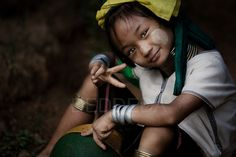 """A young female member of the """"long neck"""" Karen Tribe from Burma gives the """"peace"""" sign. The Karen Tribe are Burmese refugees. This young girl was at her refugee camp near the Burmese (Myanmar) border near Mae Hong Son in northern Thailand."""